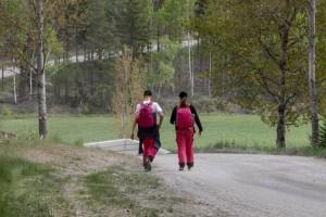 Två scouter på vandring längs väg