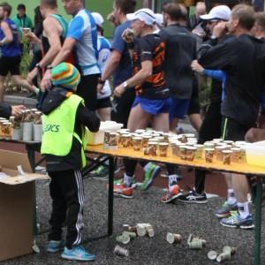 Barn delar ut vatten på Stockholm Marathon